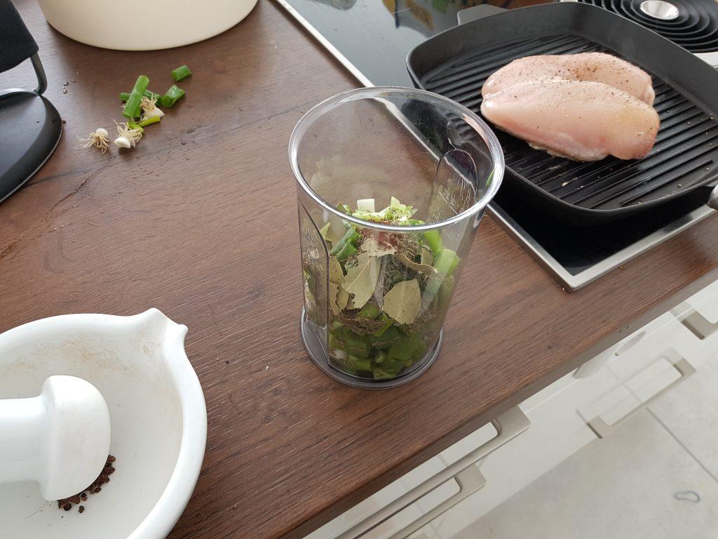 Küchenausschnitt mit Hähnchen in der Grillpfanne und Jamaikasauce im Messbecher