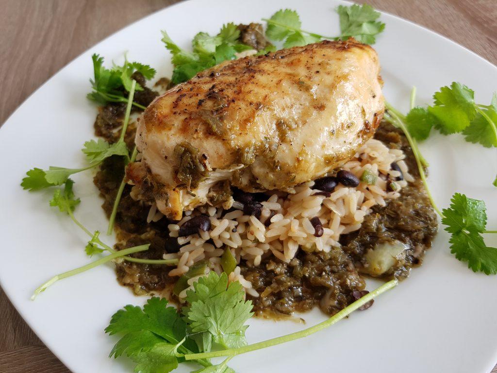 Hähnchenbrust auf Bohnen und Reis umrahmt von Sauce und Koriandergrün
